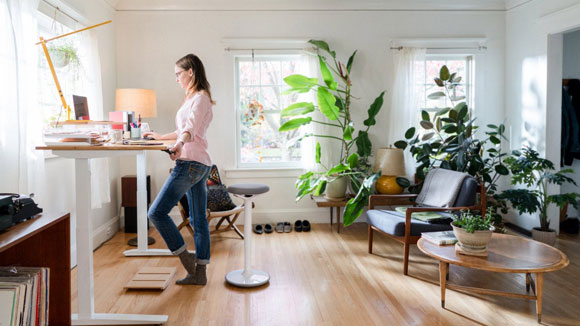 Home office plants - woman standing at desk